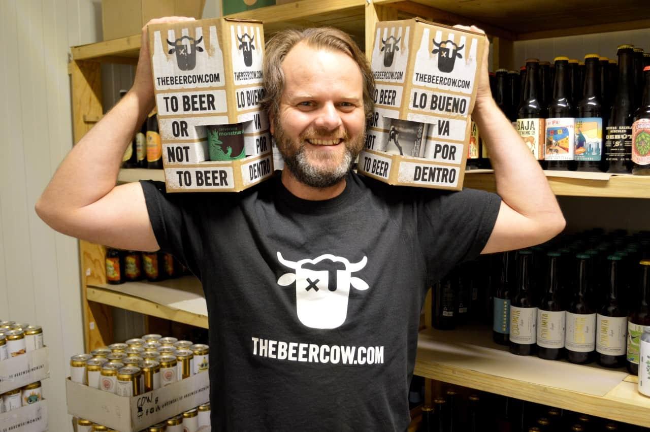 Hombre sosteinendo dos cajas de cervezas
