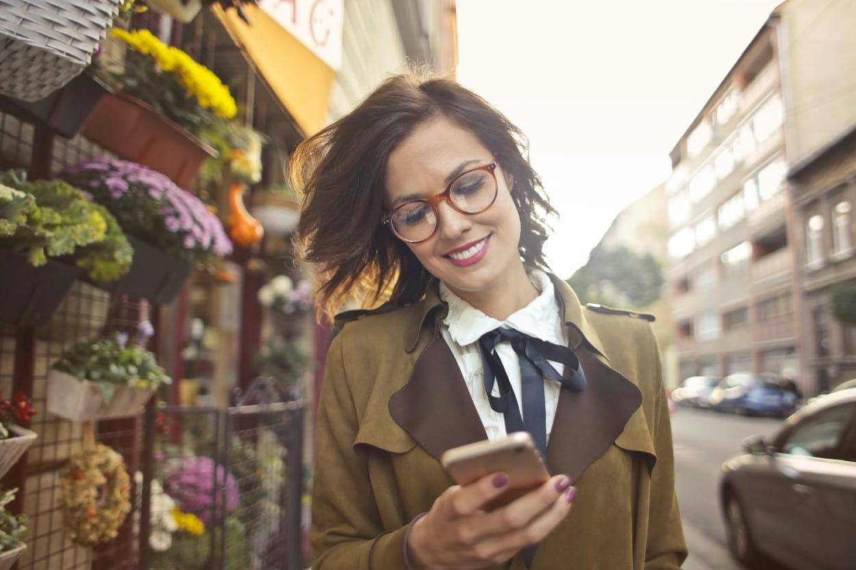 Mujer en celular pagando a distancia
