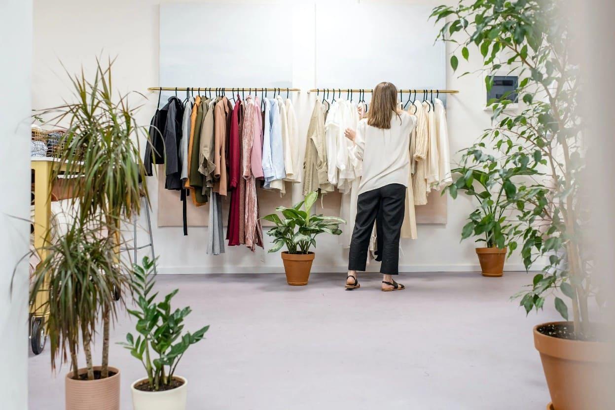 Mujer en su negocio eligiendo ropa